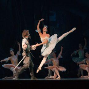 Un homme et une femme font de la danse classique, le danseur accompagne la danseuse qui fait un saut